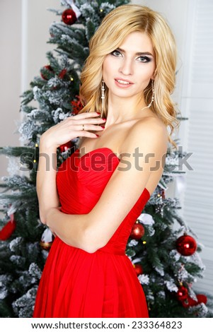 Portrait of beautiful blonde young woman in gorgeous red dress and evening make-up and hair style over christmas background - stock photo