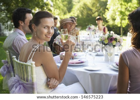 Portrait of beautiful bride holding champagne flute while sitting with guests at wedding table - stock photo
