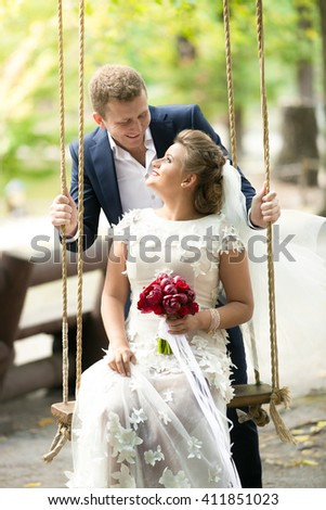 Portrait of beautiful bride sitting on swing and looking at handsome groom - stock photo