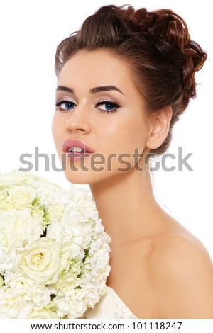 Portrait of beautiful bride with stylish make-up and hairdo holding bouquet in her hands, over white background - stock photo