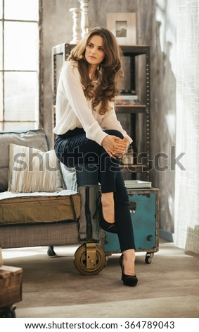 Portrait of beautiful brown-haired woman in elegant clothing sitting on couch in stylish loft apartment - stock photo