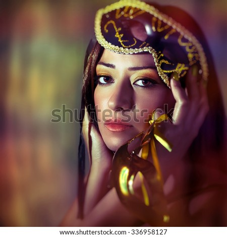 Portrait of beautiful brunet woman wearing gold Venetian mask over colorful background, luxury masquerade party on New Year eve, perfect holiday makeup, fashion portrait - stock photo