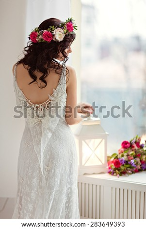 Portrait of beautiful brunette girl in a white fishnet dress with a wreath of flowers on her head, standing back near the window and a flashlight - stock photo
