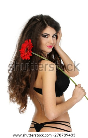 Portrait of beautiful brunette girl in black underwear with red gerbera on shoulder. Isolated on white - stock photo
