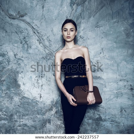 Portrait of beautiful brunette girl in the studio, holding a bag - stock photo