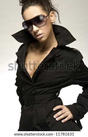 portrait of beautiful brunette girl with sunglesses and black coat - stock photo