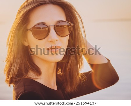 Portrait of beautiful brunette woman in round sunglasses on beach at sunny day. Image with sunlight effect - stock photo