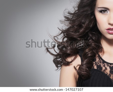 Portrait of beautiful brunette woman over grey background - stock photo
