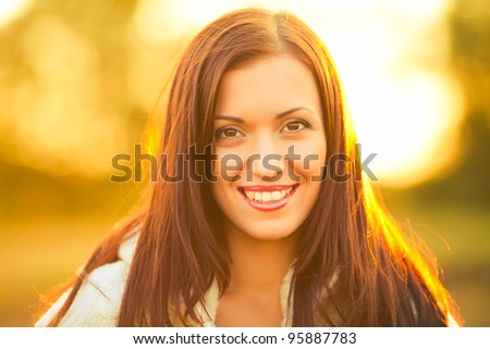 portrait of beautiful brunette young woman in countryside - stock photo