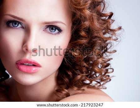 Portrait of beautiful brunette young woman with bright make up. Closeup face with curly hairstyle. - stock photo