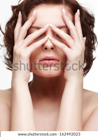 portrait of beautiful brunette young woman with french manicure closing eyes with manicured hands - stock photo