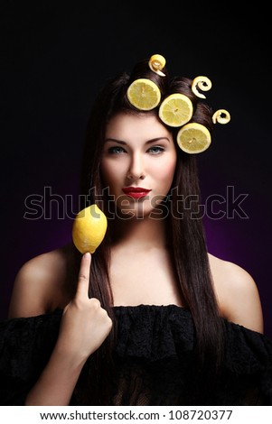 Portrait of beautiful brunnete with lemons in her hairstyle - stock photo