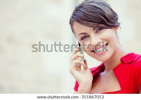 Portrait of beautiful business woman in red dress holding her mobile - stock photo