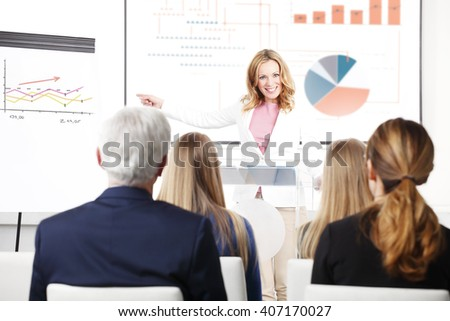 Portrait of beautiful businesswoman giving presentation at business conference to her coworkers at auditorium. - stock photo