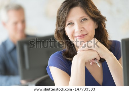 Portrait of beautiful businesswoman smiling with colleague working in background at office - stock photo