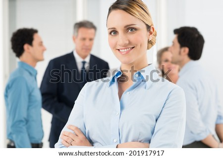 Portrait Of Beautiful Businesswoman Standing With Arm Crossed - stock photo