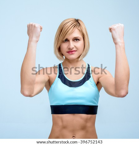 Portrait of beautiful caucasian blonde sporty woman. Young athlete showing strong arms and looking at camera - stock photo