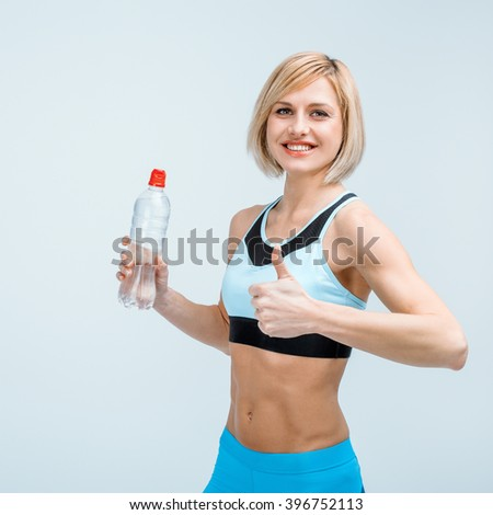 Portrait of beautiful caucasian blonde sporty woman. Young athlete showing thumb up, holding bottle of water, smiling and looking at camera - stock photo