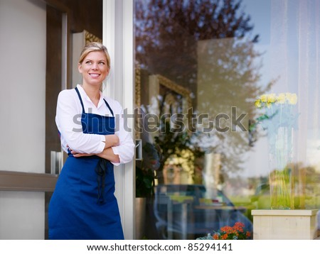 Portrait of beautiful caucasian girl self-employed in flower shop, smiling and looking away. Horizontal shape, waist up, copy space - stock photo