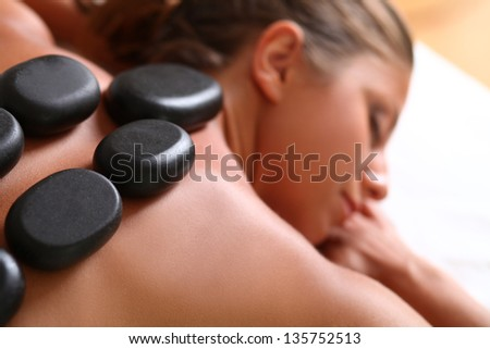 Portrait of beautiful caucasian woman with spa stones on her back - stock photo