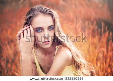 Portrait of beautiful caucasian young woman with blue eyes and long hair outdoors - stock photo
