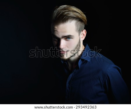 Portrait of beautiful charming young man with blue eyes and fair hair over black background, toned - stock photo