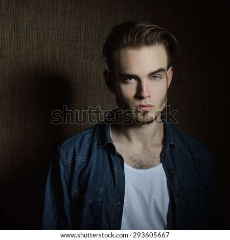 Portrait of beautiful charming young man with blue eyes and fair hair over canvas background - stock photo