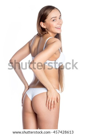 Portrait of beautiful cheerful Caucasian young woman wearing white set of lingerie. Fashion girl in bra and panties posing on white background, smiling, looking at camera. Studio image. Back view - stock photo