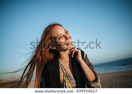 Portrait of beautiful cheerful red-haired girl looking away in sunlight against of sea and blue sky. - stock photo