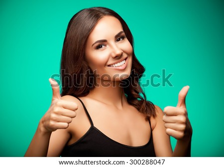 Portrait of beautiful cheerful smiling young woman in black tank top clothing, showing thumb up gesture, on green background - stock photo