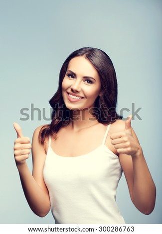 Portrait of beautiful cheerful smiling young woman in white tank top clothing, showing thumb up gesture, with blank copyspace area for text or slogan - stock photo