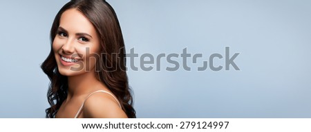 Portrait of beautiful cheerful smiling young woman, over grey, with blank copyspace area for text or slogan - stock photo