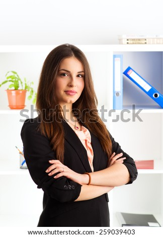 Portrait of beautiful confident female CEO standing with crossed arms. Young professional businesswoman in the office. - stock photo