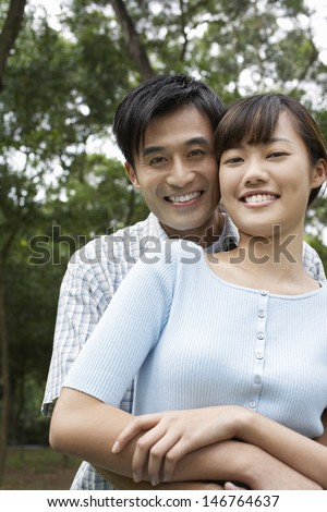 Portrait of beautiful couple embracing in park - stock photo