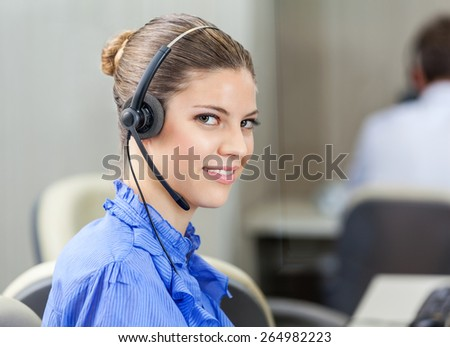 Portrait of beautiful customer service executive wearing headset in call center - stock photo