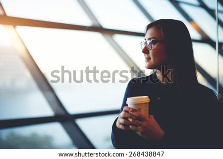 Portrait of beautiful cute girl sitting near big window with coffee take away in airport, filtered image - stock photo