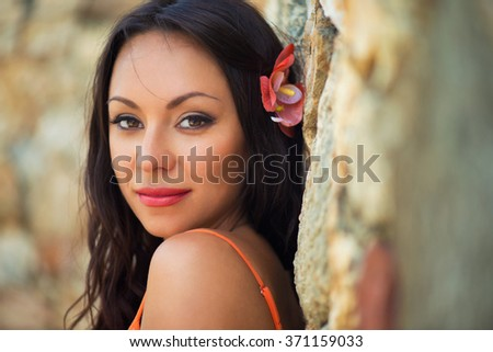 Portrait of beautiful dark-haired smiling girl against the backdrop of medieval stone buildings in the town of Altos de Chavon, Dominican Republic - stock photo