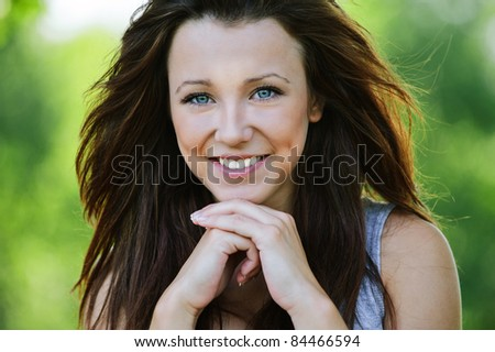 Portrait of beautiful dark-haired smiling girl propping up her face at summer green park. - stock photo