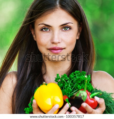 portrait of beautiful dark-haired smiling girl set with vegetables and herbs (eggplant, Bulgarian pepper red and yellow, dill and parsley) in hands on green background - stock photo