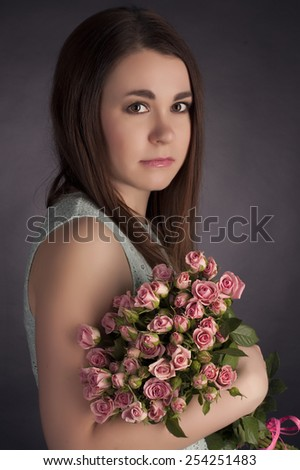 Portrait of beautiful dark-haired woman with flowers.  - stock photo