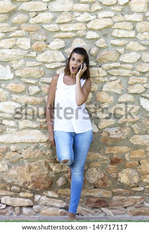 Portrait of beautiful dark-haired young woman wearing white t-shirt, surprised for the mobile - stock photo