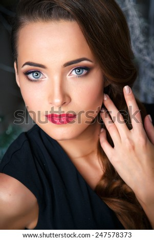 portrait of beautiful elegant young woman in gorgeous evening dress over christmas background - stock photo