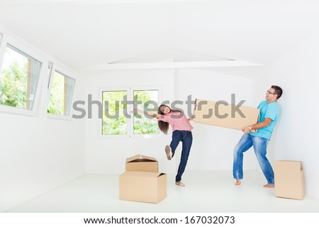 Portrait of beautiful, excited woman and man holding unpacking cardboard boxes in new home - stock photo