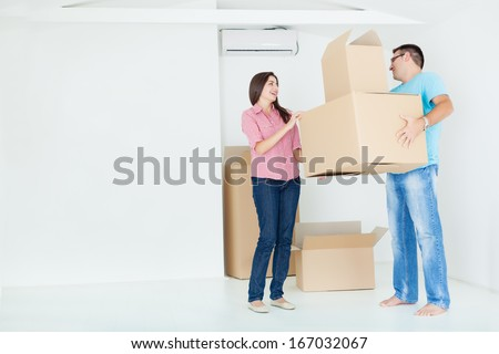 Portrait of beautiful, excited woman and man holding unpacking cardboard boxes in new home,copy space - stock photo