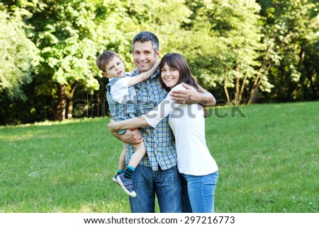 Portrait of beautiful family having fun on a meadow - stock photo