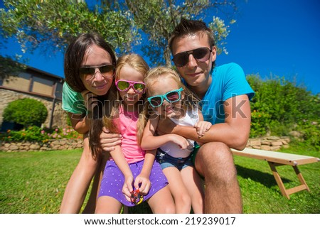 Portrait of beautiful family of four on tropical vacation - stock photo