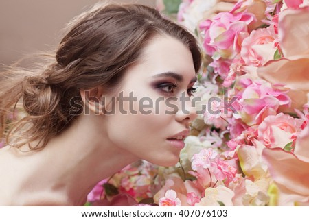 Portrait of  beautiful fashion girl, smelling a many flowers. Beautiful makeup and messy romantic hairstyle. Flowers background. Green eyes.  - stock photo