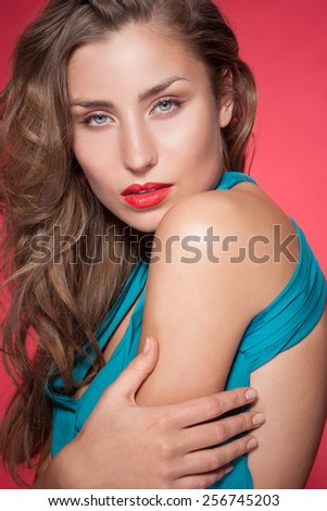 Portrait of beautiful fashion model in blue dress on red background - stock photo