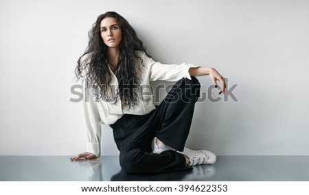 Portrait of beautiful fashion woman sitting on the floor - stock photo