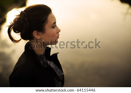 Portrait of beautiful fashionable young Asian woman outdoor by river surface background. Sepia toned, shallow DOF. - stock photo